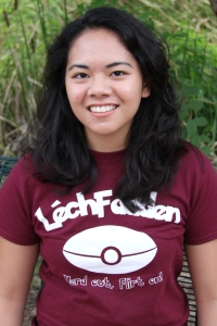 Female student with long dark hair in a maroon and white t-shirt