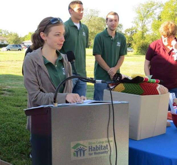 A female student with long brown hair pulled back, wearing a grey sweatshirt over a green polo speaks at a podium with several people in the background.
