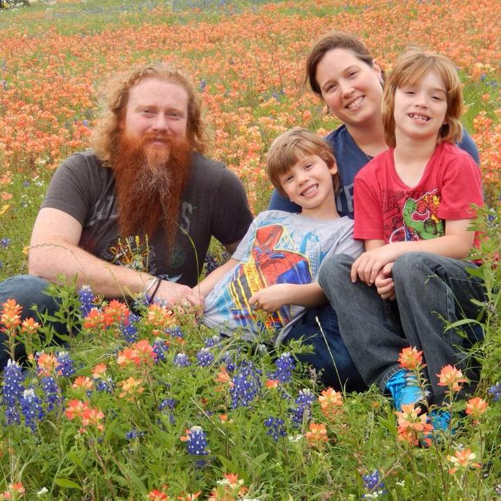 A man with long red hair and beard sits with a woman and two boys in a field of wildflowers.