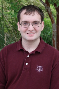 Male student with short dark hair and glasses, wearing a maroon polo shirt.
