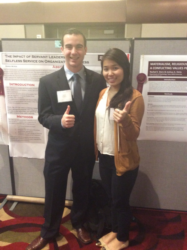 A male student in a dark suit and a female student in a brown jacket and dark skirt give a thumbs up in front of their research posters.