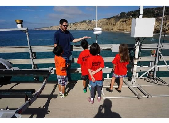 Dillon Amaya, Meteorology and Atmospheric Sciences '14, shows oceanographic instruments to 5th graders on a tour of the research pier at the Scripps Institution of Oceanography in San Diego.