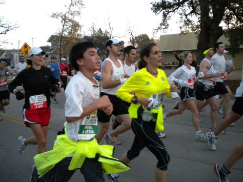 Men and women run down a residential street wearing race bibs.