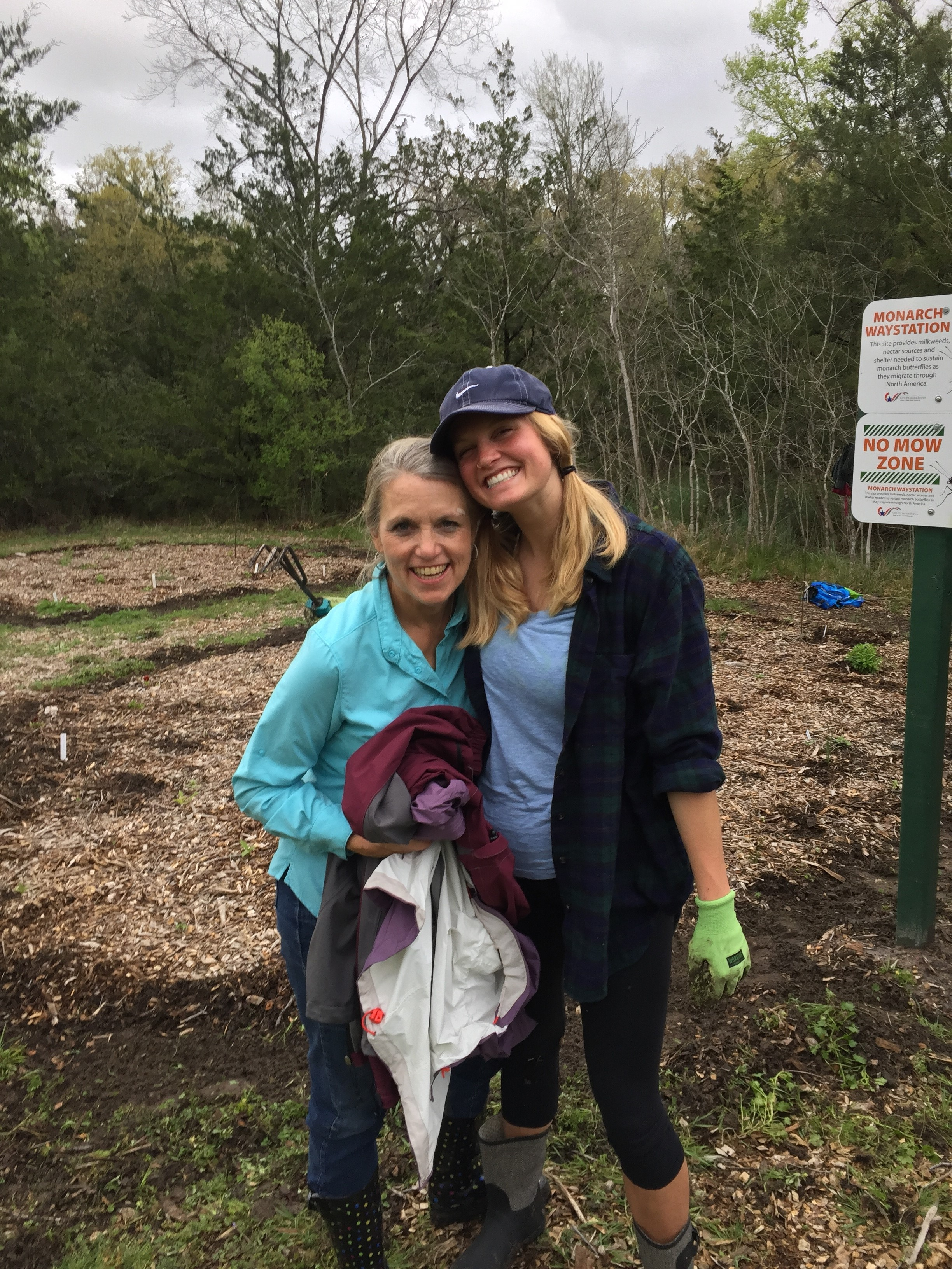 Two women smile and hug in front of a newly mulched garden.