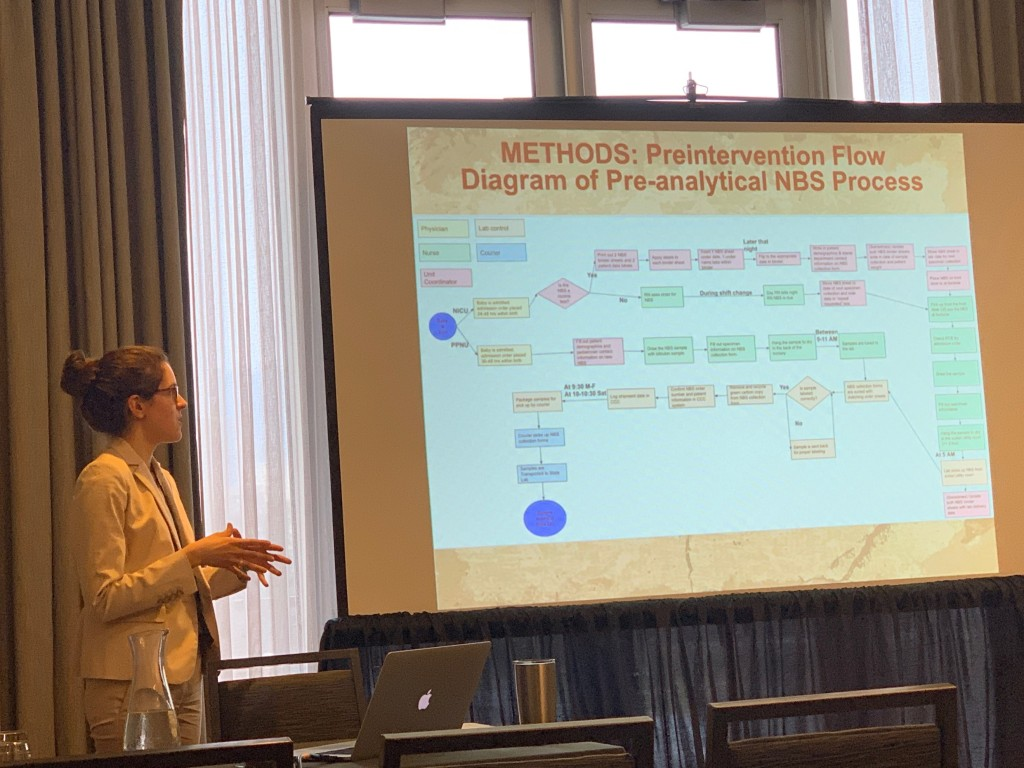 """A woman in a white suit stands in front of a draped window by a screen showing a flowchart slide titled """"Methods: Preintervention Flow Diagram of Pre-analytical NBS Process"""""""