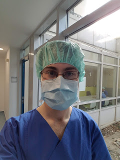 A man in blue scrubs wearing a surgical mask and cap