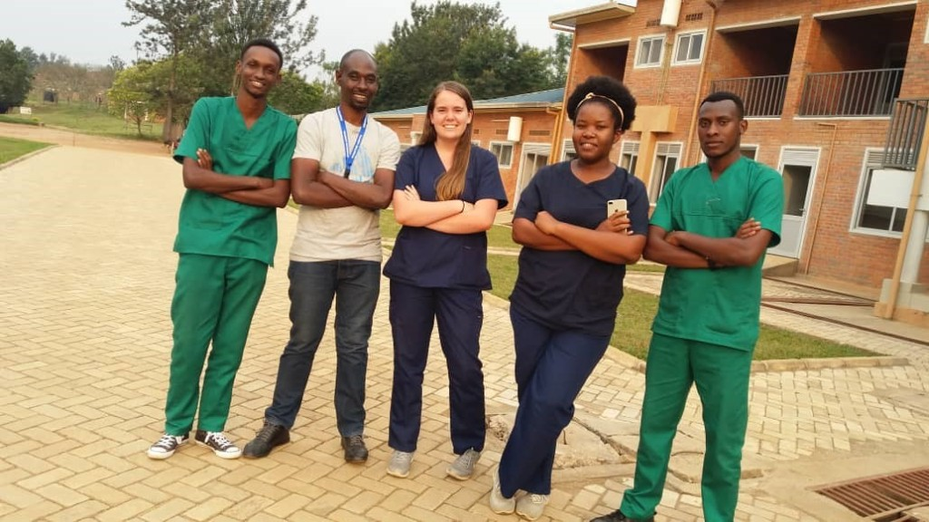 A team of five people in medical scrubs pose with crossed arms in front of a building