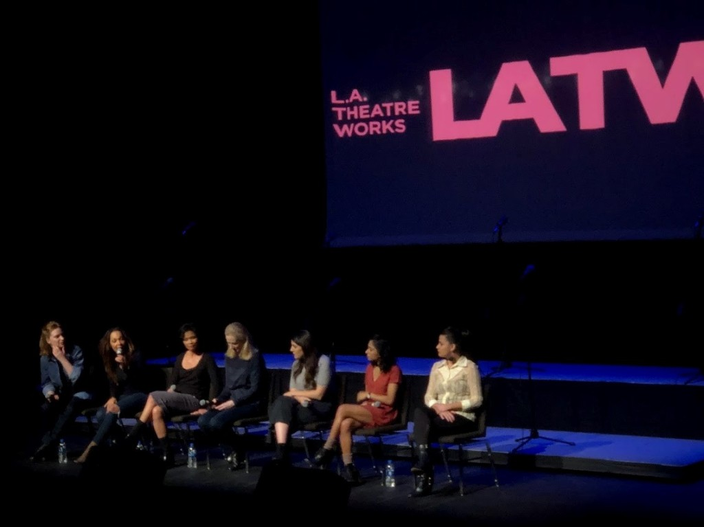 Seven women sit on a dark stage with blue lights and a pink L.A. Theatre Works logo in the background