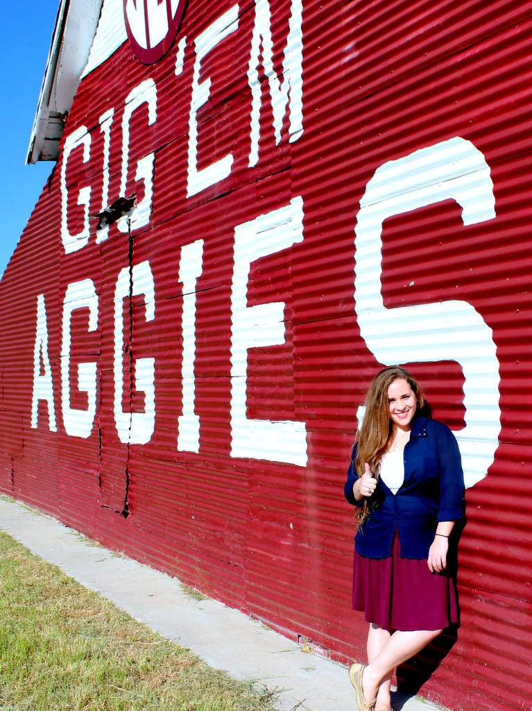 """A woman leans agains a corrugated metal barn painted marron with """"Gig Em Aggies"""" painted on it in white."""